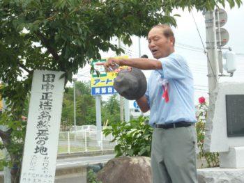 挨拶する庭田隆次さん。左側にあるのが今までのトタン板製看板